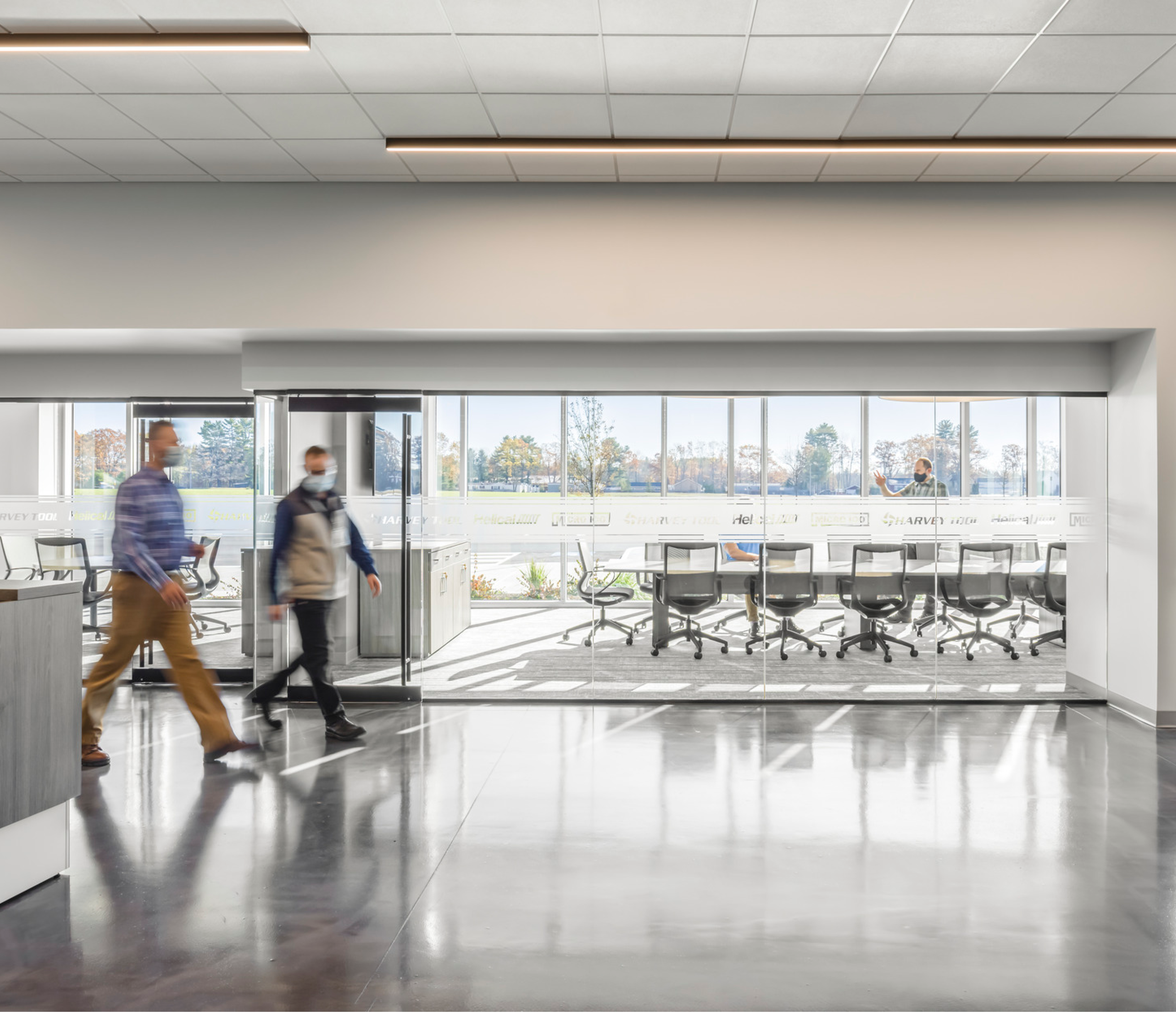 Harvey Performance Company Manufacturing Facility | Lobby and Conference Room | SMMA Design | Masked people walking through lobby