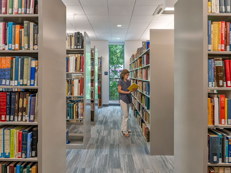 Woman browsing books in the NAASR Armenian library in Belmont Massachusetts